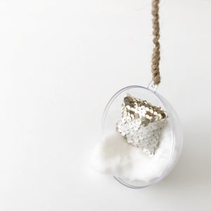Image of Hanging bubble chair with white shag throw and rope