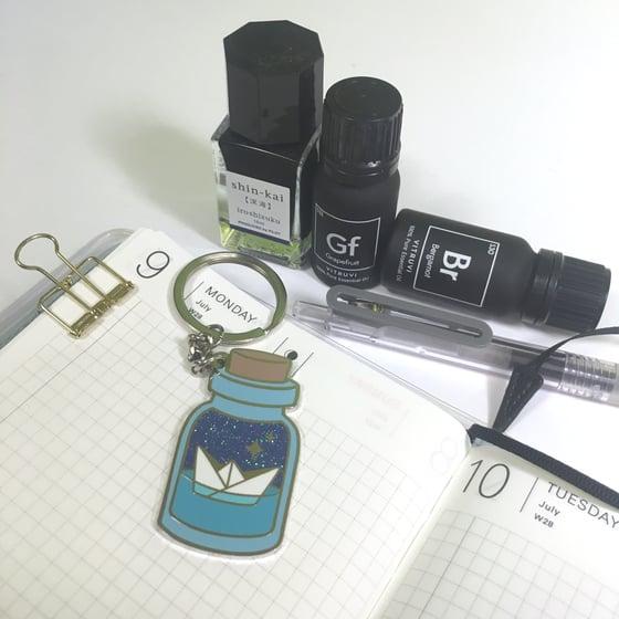 "Image of potion for safe passage | 2"" enamel keychain"