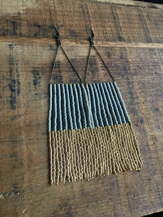 Image of Cream, matte black, and gold vertical stripe fringe earrings