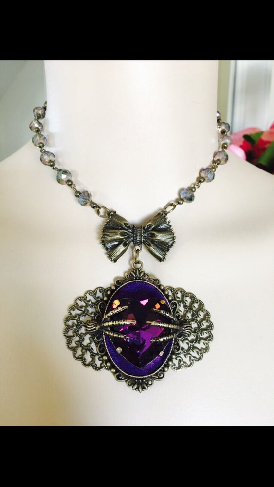 Image of Sinister Claws Clutching A Beautiful Purple Heart Rhinestone