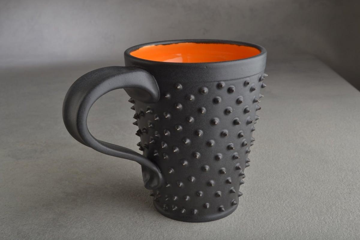Image of Spiky Mug Gun Metal Black and Orange Made To Order By Symmetrical Pottery