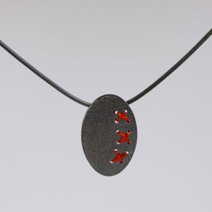 Image of Sewn Up oval pendant with 3 kisses