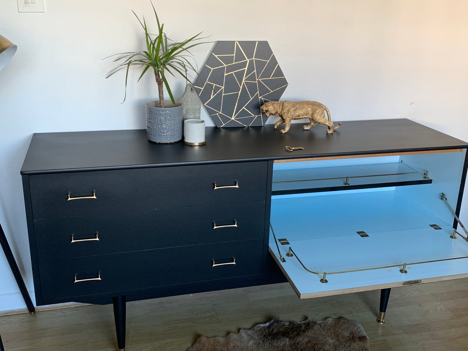 Image of A black and gold drinks sideboard with key.