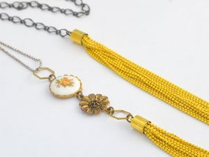 Image of vintage yellow rose linked with a chunky strands of mustard yellow chain