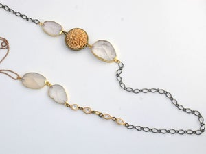 Image of long strand necklace with faceted crystals and a vintage carved floral