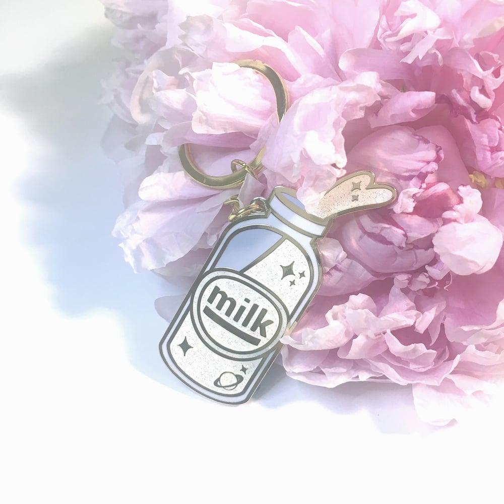 "Image of spilled milk | 2"" enamel keychain"