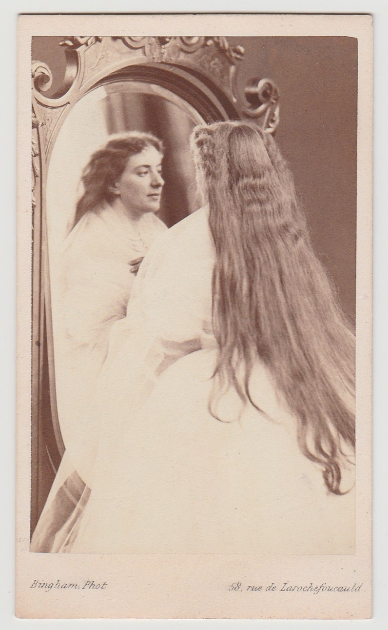Image of Bingham: actress Achard with long hair looking in a mirror, ca. 1865