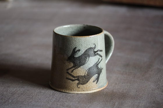 Image of Hare and Rook Mug. Blue Celadon glaze. With Oxidized yellow limited edition