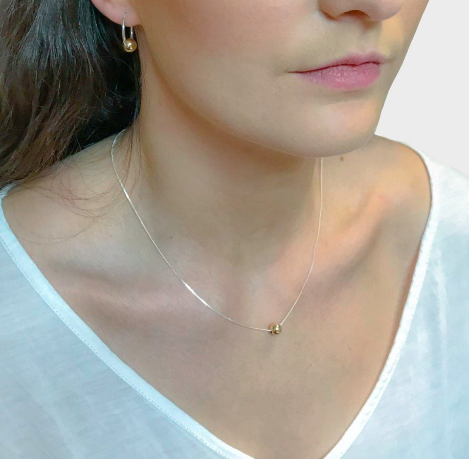 Image of Silver necklace with a single 9ct gold bead