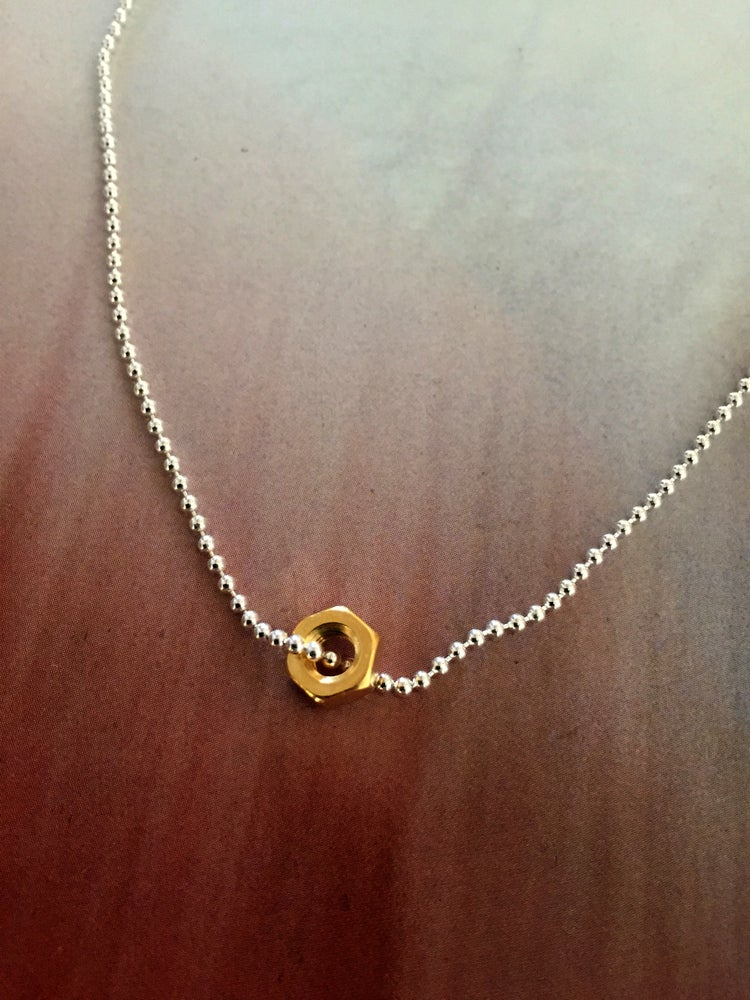 A fine bead and ball sterling silver chain necklace 32cm long, calm and elegant in proportions with a whip of gold in the shape of a gold nut.