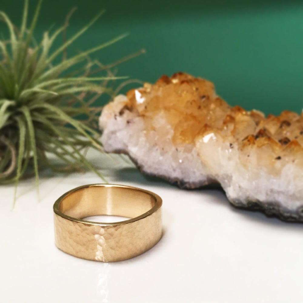 Image of wide hammered band in 14k yellow gold, finger shaped design
