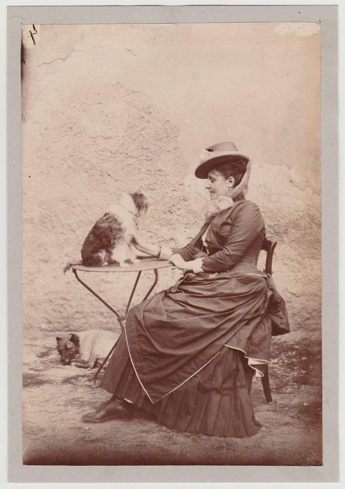 Image of Anonymous: Woman posing outside with two dogs, ca. 1880
