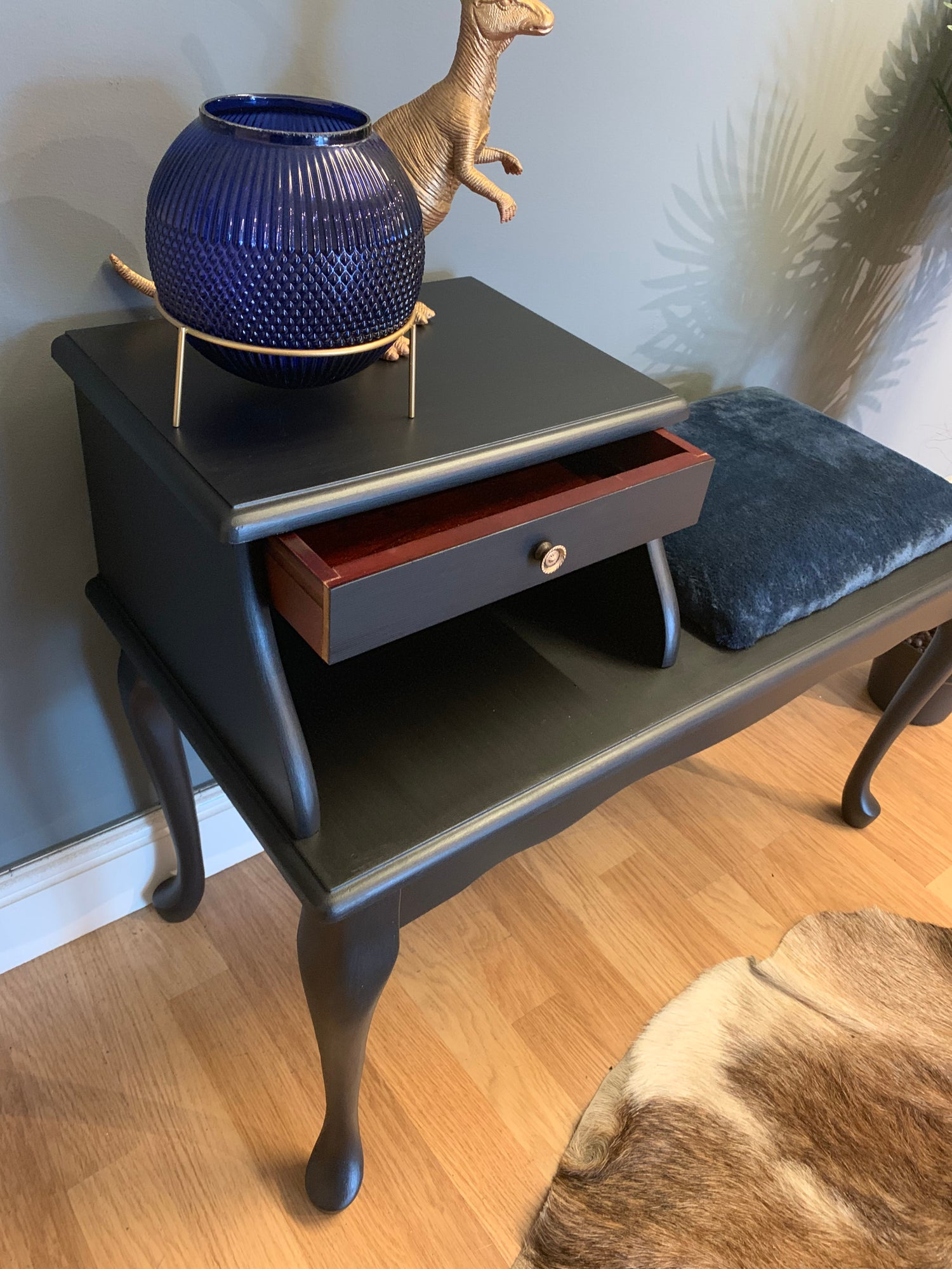Image of A black telephone table with a navy blue fluffy seat.