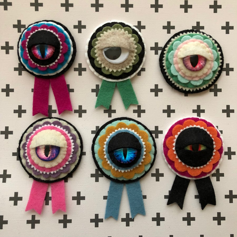Image of EYE on the prize ribbon brooches
