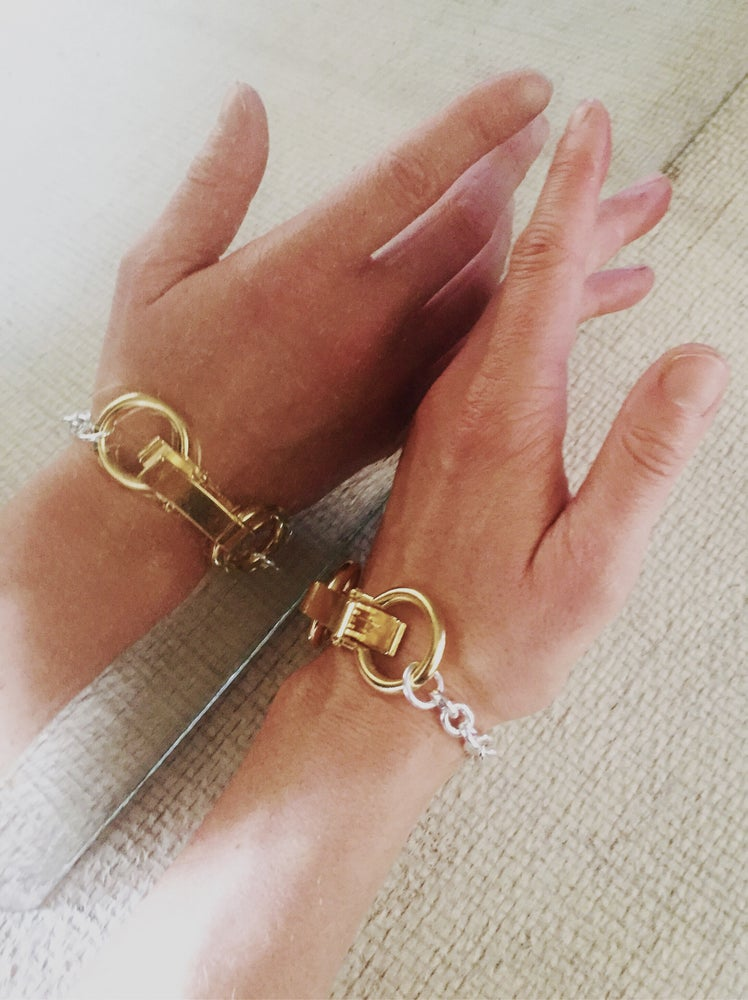 This bracelet is adorned with a new big gold plated hardware clip clasp.