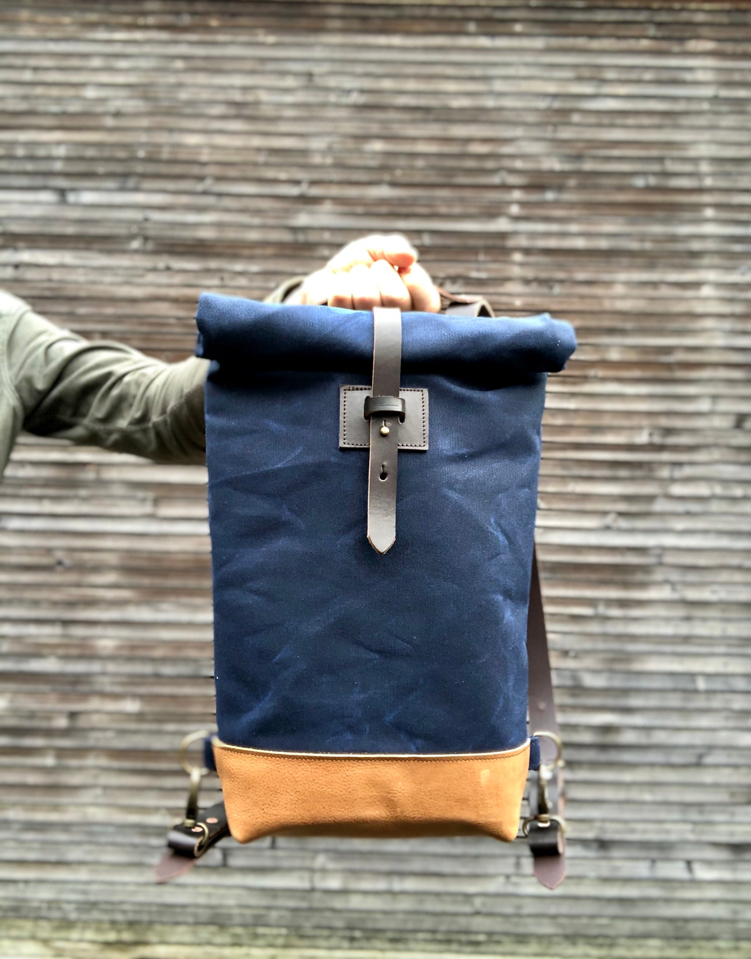 Image of Small waxed canvas backpack in navy blue with rolled top and leather shoulder straps