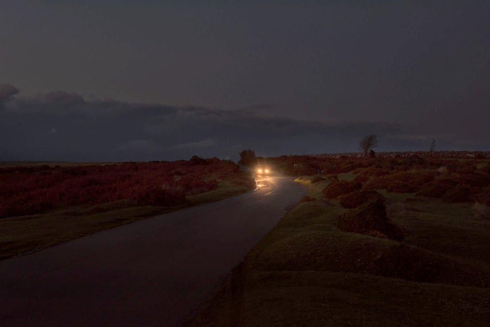 Image of DARTMOOR, CAR HEADLIGHTS, DUSK