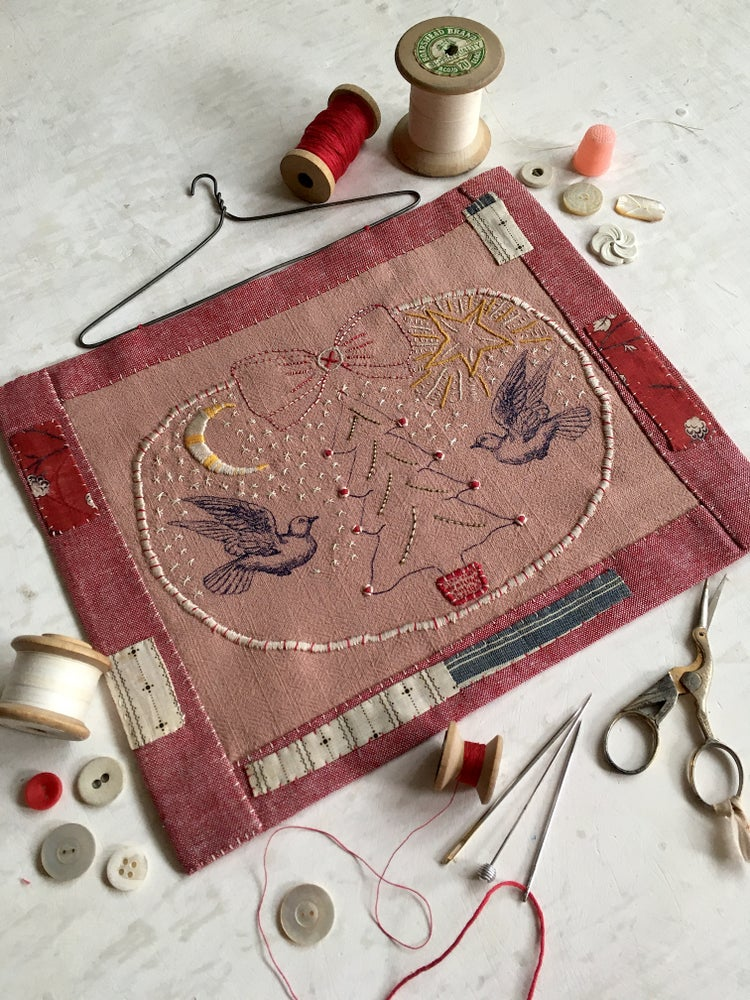 Image of 'Christmas time' embroidery template on soft pink fabric
