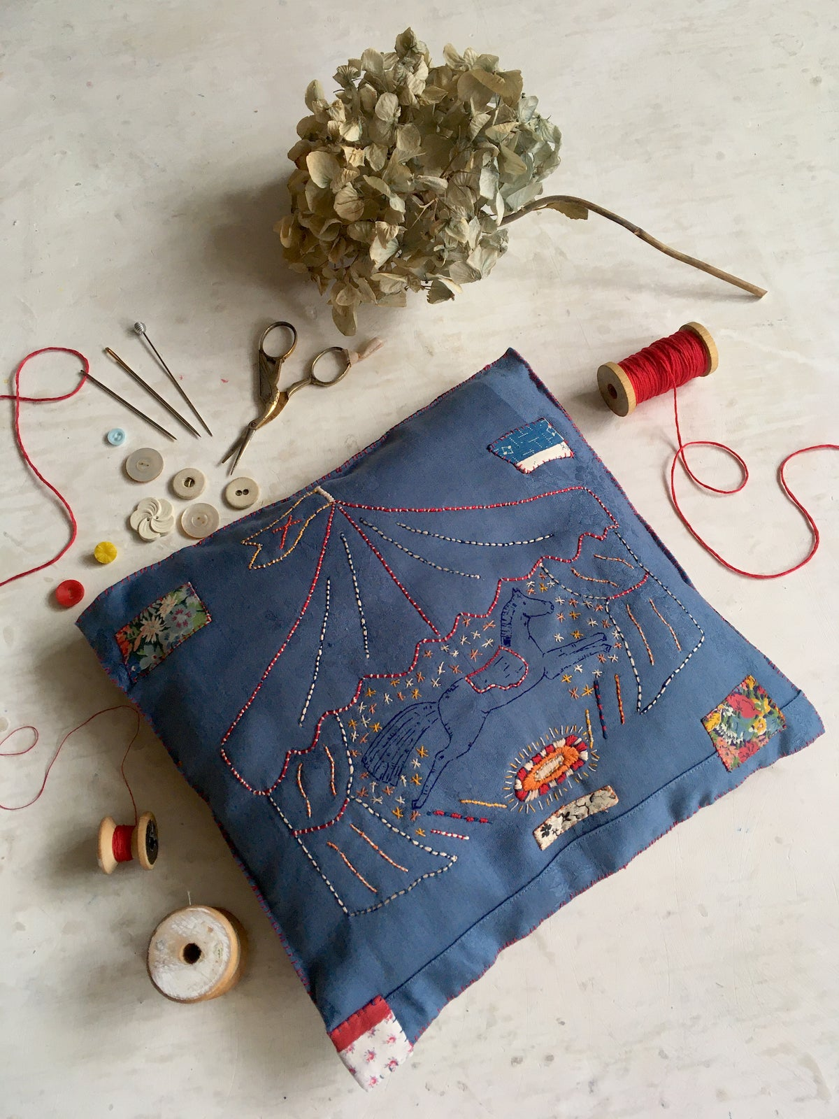 Image of 'Le Cirque' embroidery template on hand dyed blue fabric