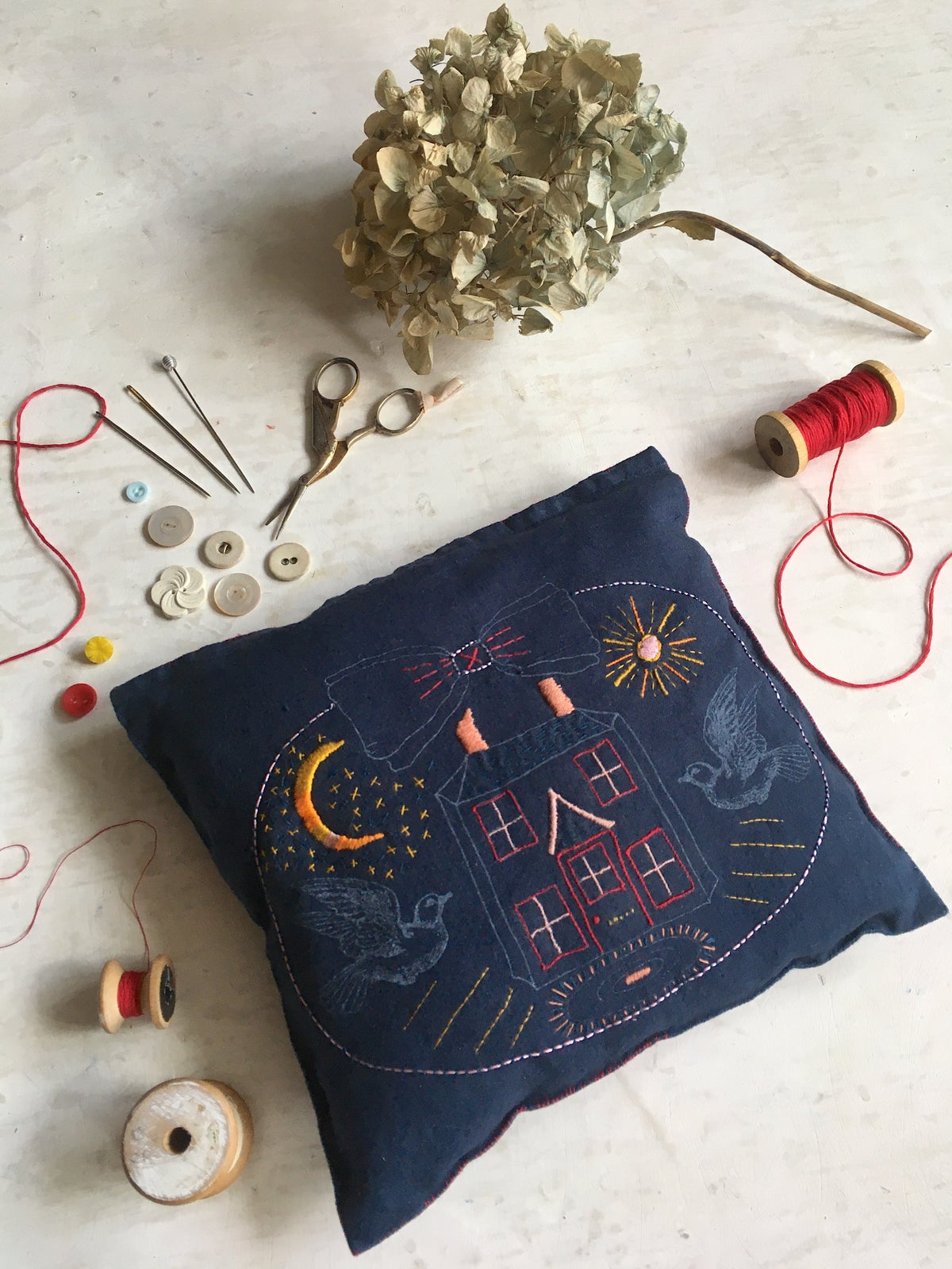 Image of 'Doves & Home' embroidery template on hand dyed blue fabric