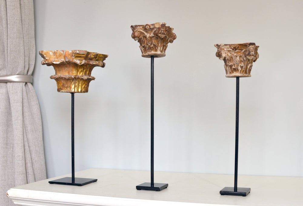 Image of A group of antique capitals on stands