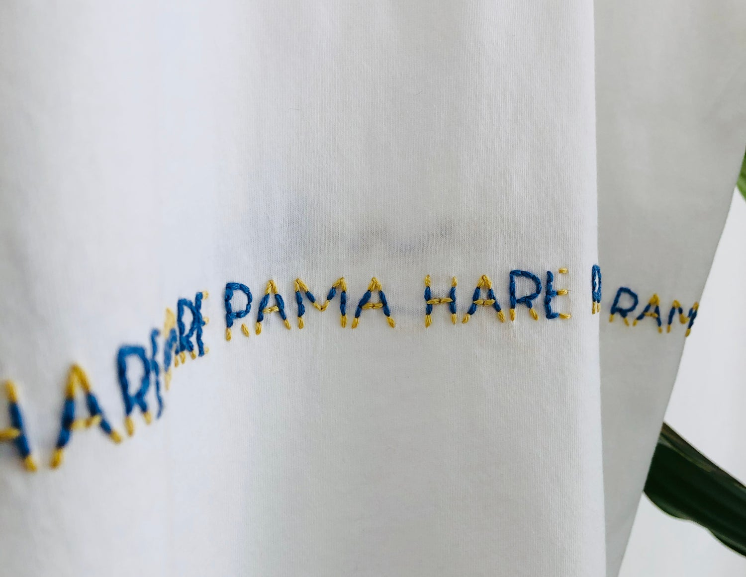 Image of MAHA MANTRA – wrapped – blue/yellow – white t-shirt w/ rolled-up sleeves