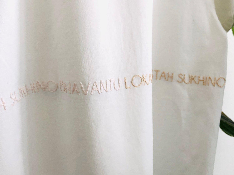 Image of LOKAH SAMASTAH SUKHINO BHAVANTU – wrapped – light blue/beige/rose – white unisex t-shirt
