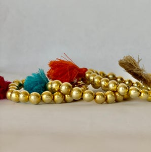 Image of gold balls on elastic with tassels