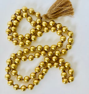 Image of round gold bead neck with tassel