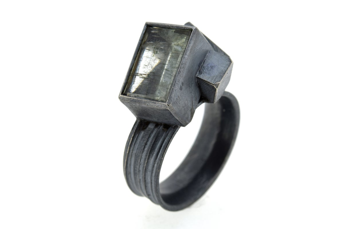 Sculptural silver ring set with mirror cut aquamarine with goethite inclusions. Chris Boland