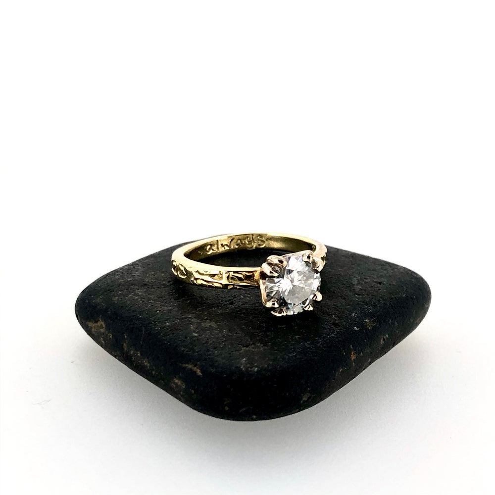 Image of grey moissanite engagement ring in 18k gold