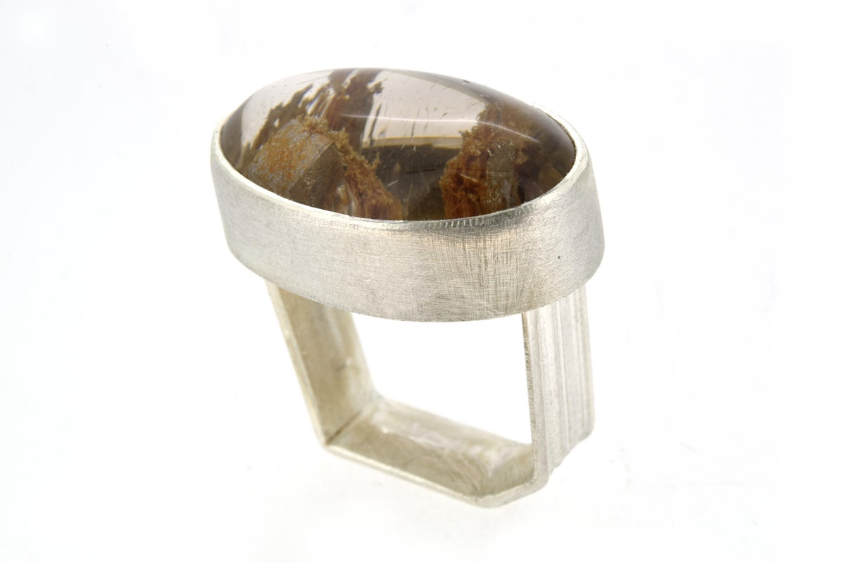 A monolith ring in sterling silver with oval Quartz with chlorite and calcite cube inclusions,