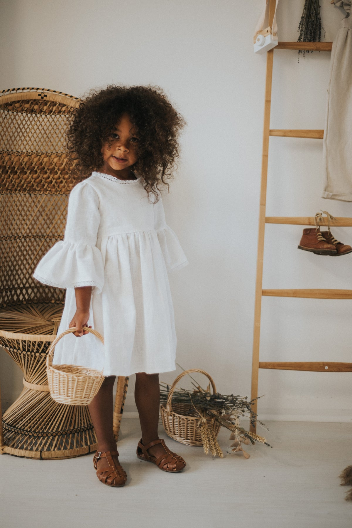 White linen forever dress with large bell sleeves and lace detail