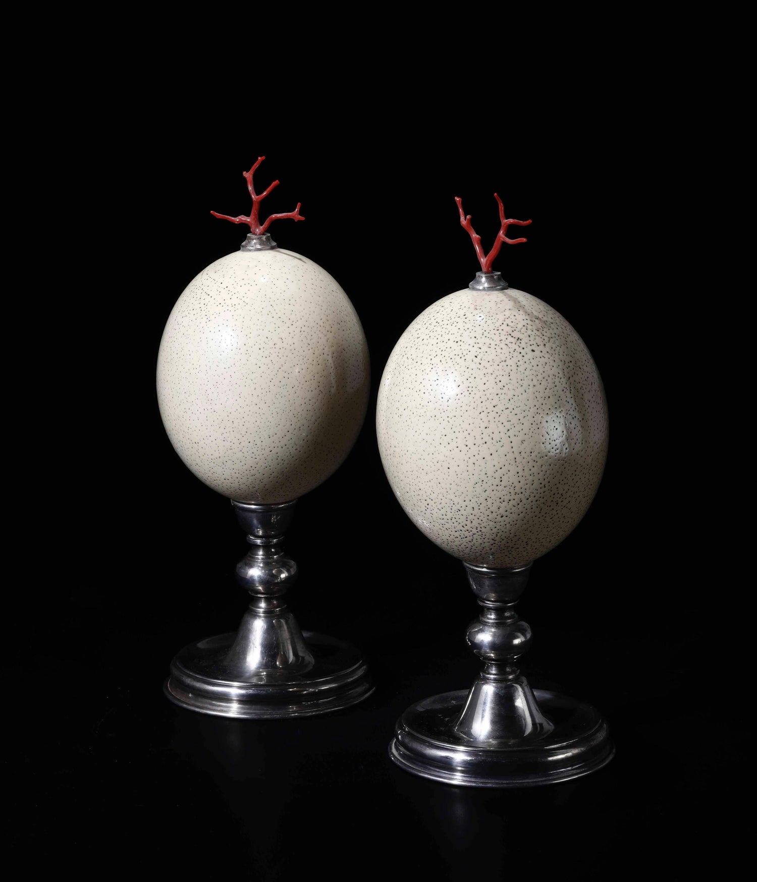 Image of Pair of exotic ostrich eggs with red coral sprigs mounted on silver display stands