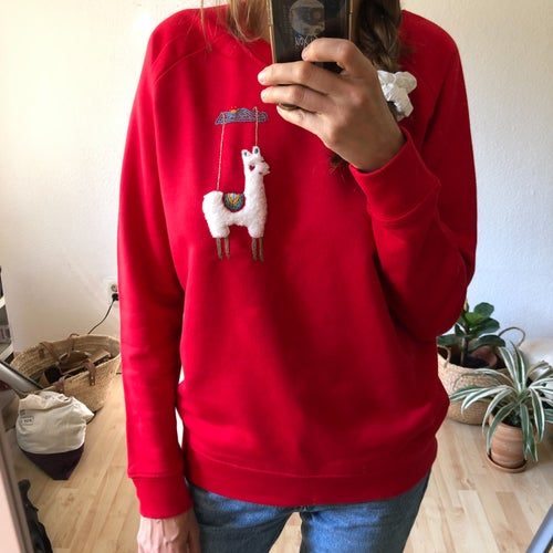 Image of Smitten alpaca on a red sweatshirt, hand embroidered, organic cotton, GOTS certified