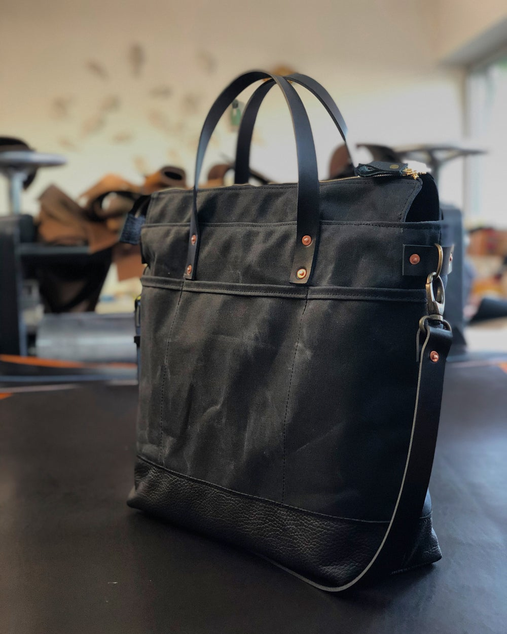 Image of Black waxed canvas tote bag / office bag with luggage handle attachment leather handles and shoulder