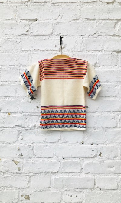 Image of Short sleeved, cream sweater with red, yellow and blue stripes. Age 2-3yrs.
