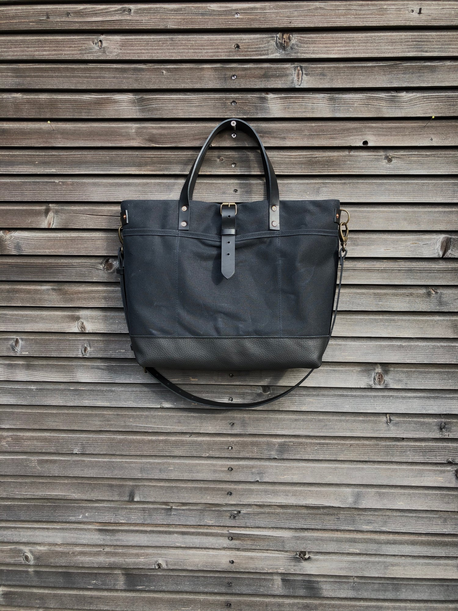 Image of Black tote bag in waxed canvas with leather bottom and cross body strap