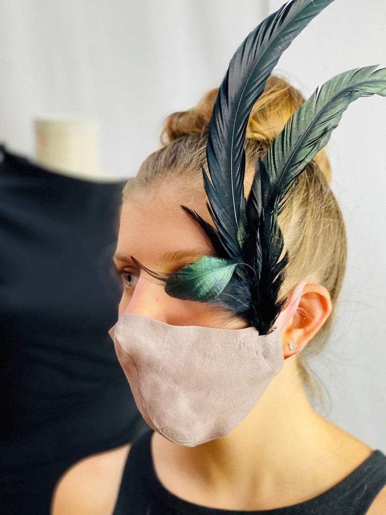 Image of fascinator with feather in flesh