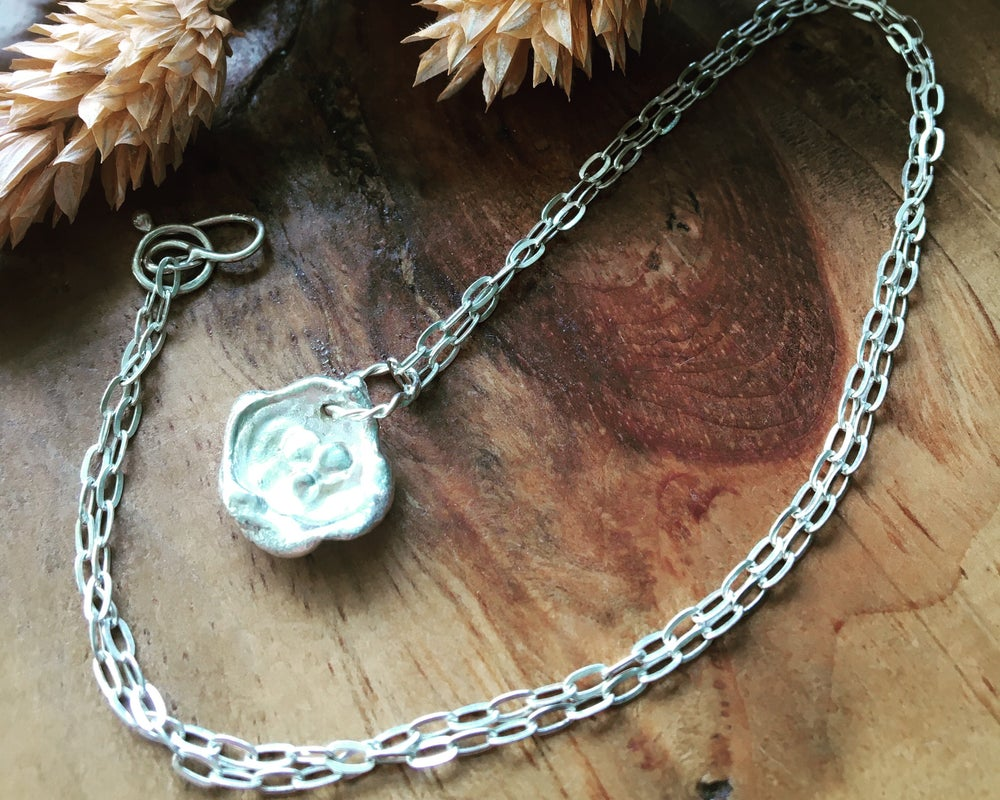 Image of Delicate shell-shaped silver water cast necklace on a 16 inch chain