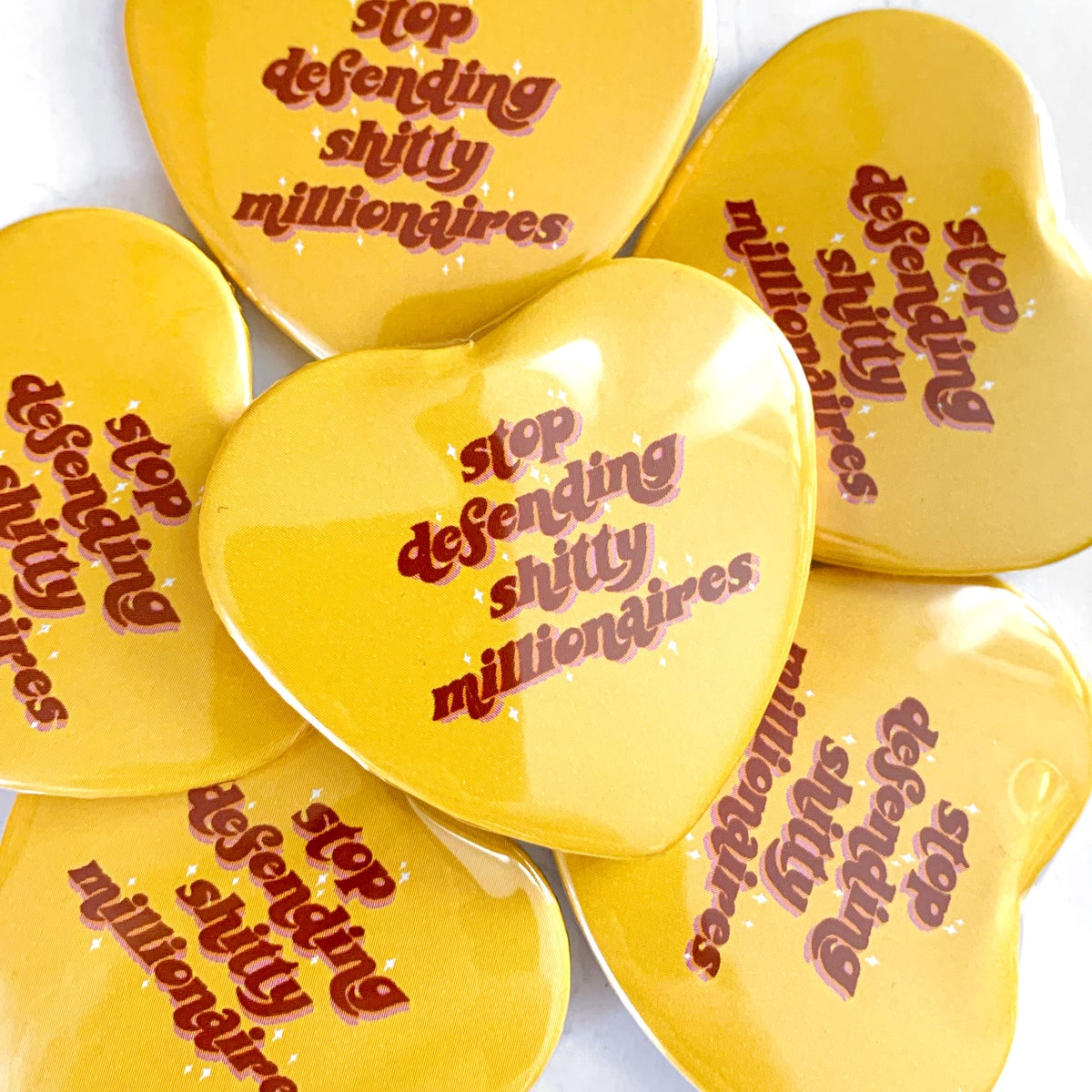 Image of STOP DEFENDING SHITTY MILLIONAIRES - HEART SHAPED BUTTON