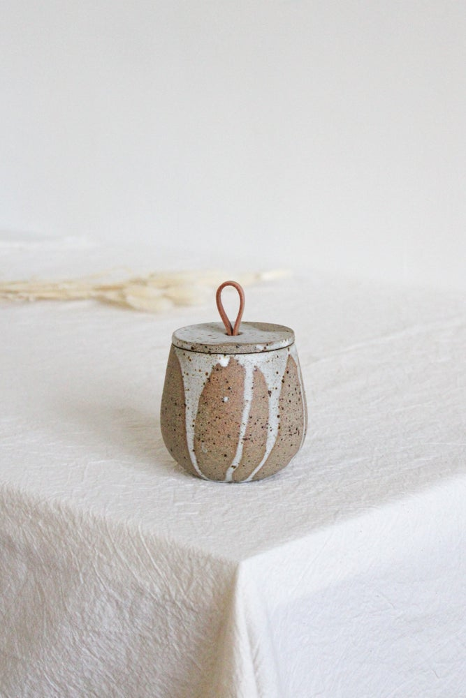 Image of lidded jar with a leather handle
