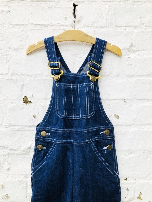 Image of Dark indigo denim dungarees with white contrast stitching. Age 4-6yrs.