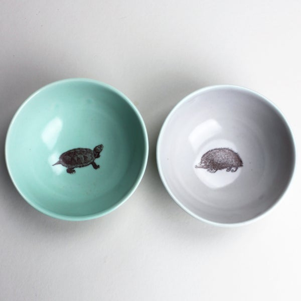Image of roly-poly bowls, set of two, aqua with turtle, lilac-grey with hedgehog