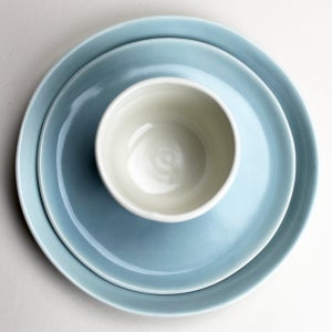 Image of good morning set: wee tea cup, two plates, ocean with warbler