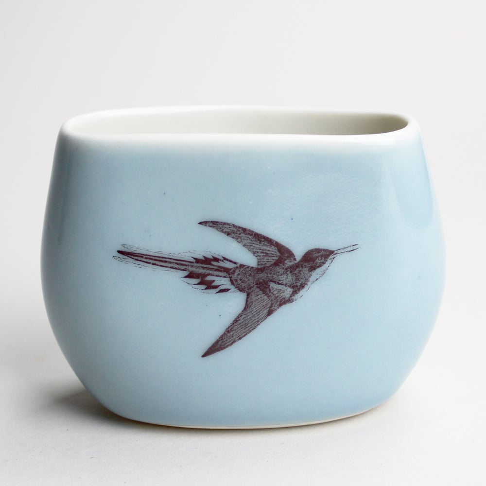 Image of pebble vase, ocean, hummingbird