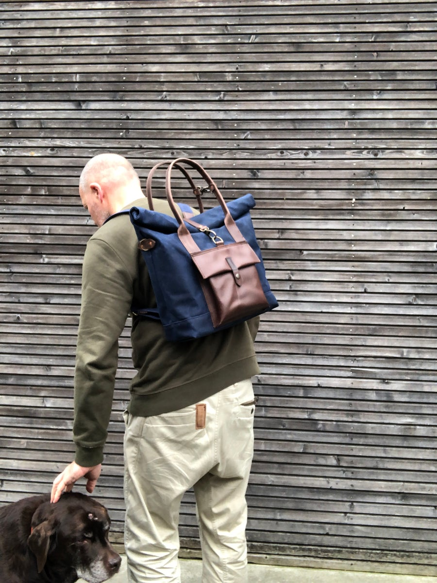Image of Convertible backpack in waxed canvas with leather outside pocket and cross body strap