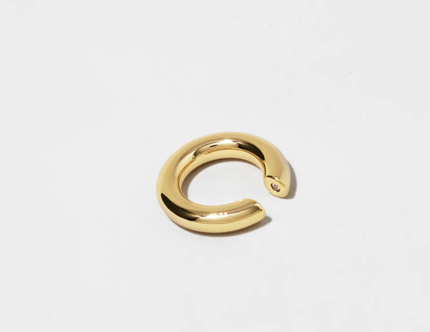 THOUGH IN A DIFFERENT WAY  The Eclipse cuff is timeless in its simplicity and bold look. This piece consists a round tube that will hug you ear without the need of being pierced. Slip thecuffover the thinnest part of yourear, which is usually at the top and then slide it down to where it sits comfortably and securely.  This piece becomes the perfect daily companion. Heavy gold plated brass.  Sold as a single piece, but possible to buy a set too (see options)