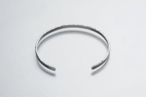 Image of thin silver bracelet with inscription in Latin