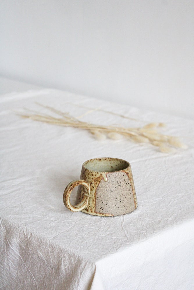 Image of handled mug in yellowish glaze